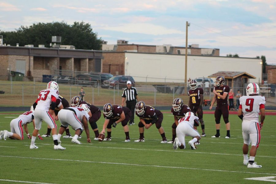 The+offensive+line%2C+%232+Kadarrius+Walker%2C+and+%238+Chad+Rushin+prepare+for+the+snap.+Photo+by+Melanie+Pina.