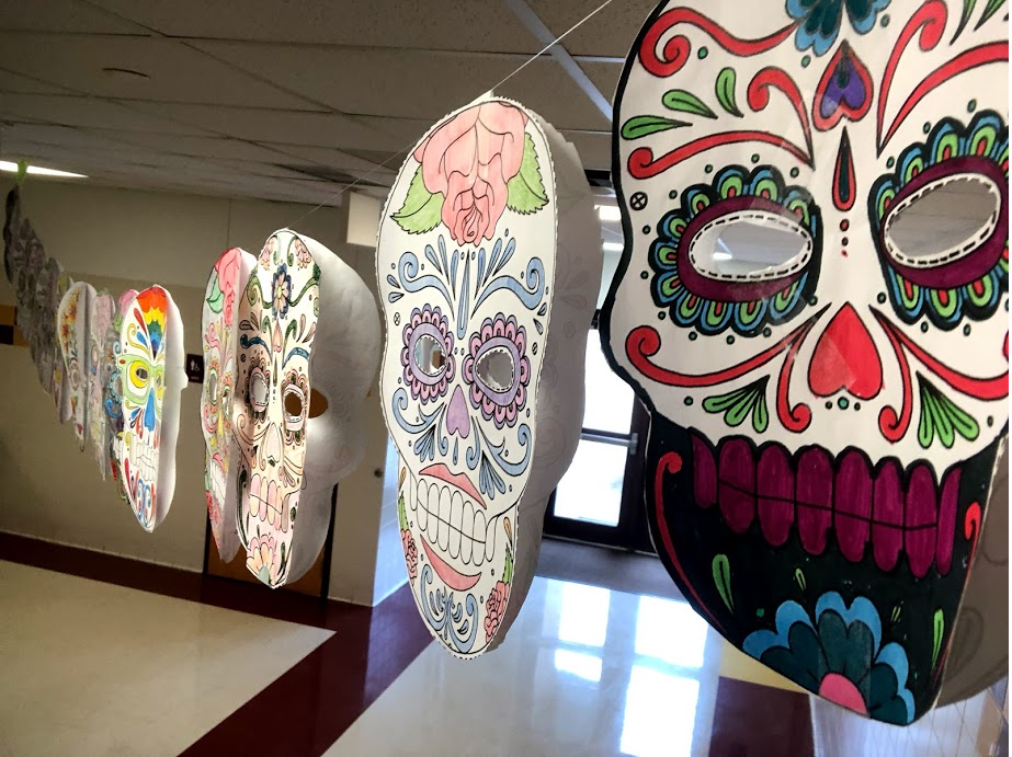 Student-created Day of the Dead masks hang in the T-wing hallway.