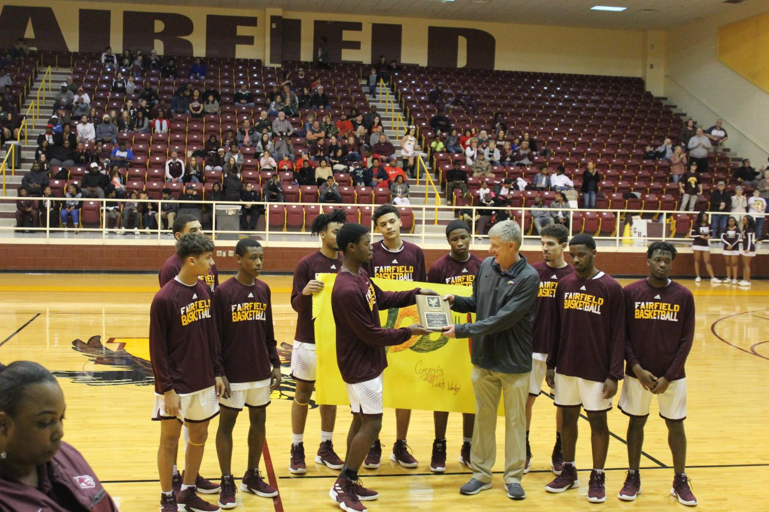 Senior Jaise Oliver presents coach Joey Worley with a plaque for his 400th win as a Fairfield basketball coach. Also pictured is the rest of the varsity basketball team. Photo by Paige Allen.