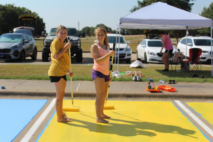 Senior Madi Isaacs and sophomore Mackenzie Isaacs paint Madi's spot. Photo by Emi Bonner