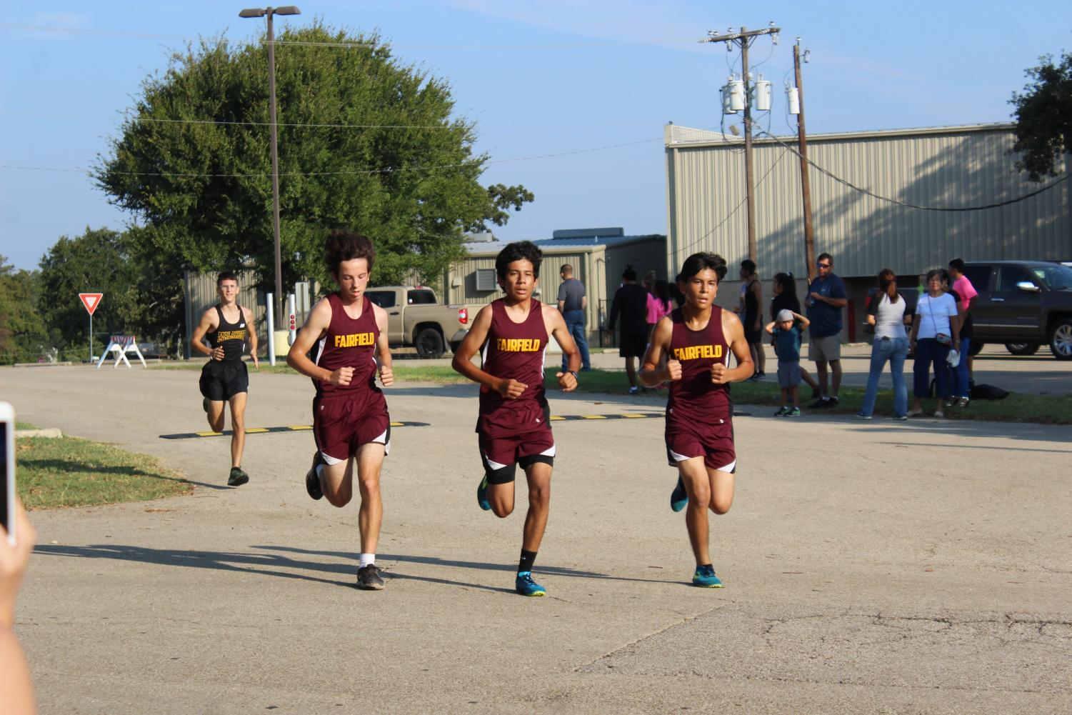 Junior Landen Espinoza, Nicholas Salazar, and Kevin Ramos race to the finish line at Teauge meet. Photo by Braden Bossier.
