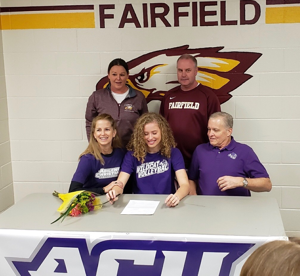 Senior Braden Bossier signs in front of her family, coaches, and friends. Photo by Kathie Maciel.