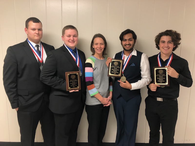 Advancing debaters junior Robby Walia, sophomore Kelton Carleson, seniors Klay Bonner and Devin Johnson hold their awards with CX sponsor Nicole Crawford. Photo contributed by FHS.