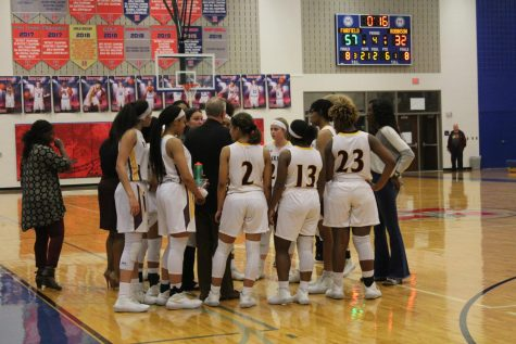 Lady Eagles call a time out to plan their strategy for the game. Photo by Cate Scott.