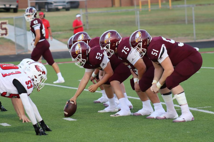 Offensive players line up against Rusk Eagle at home on August 28. Pictured: #52 senior Carson Moore, #75 junior Bosque Monico, and #51 junior Riley Armstrong.