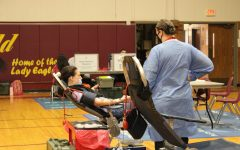 Senior Dylan Pickens rolls up her sleeves to give blood at the blood drive.